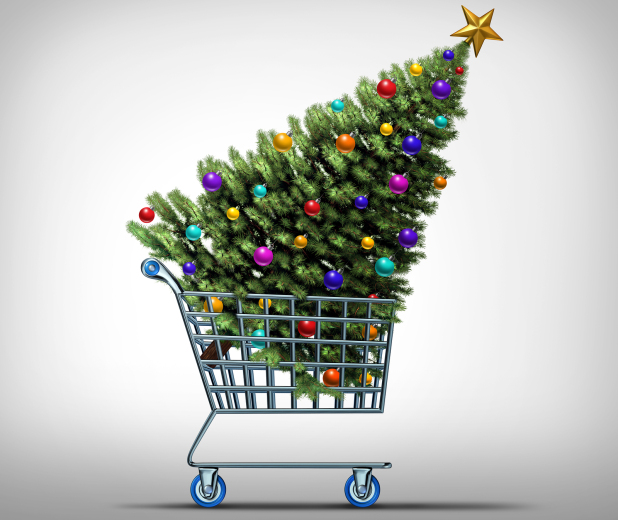 Christmas shopping concept as a store shop cart hauling a decorated festive holiday pine tree as a symbol for black friday sale or purchasing gifts and sales online.